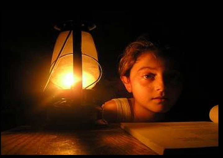 Libyan Boy studies by oil lamp