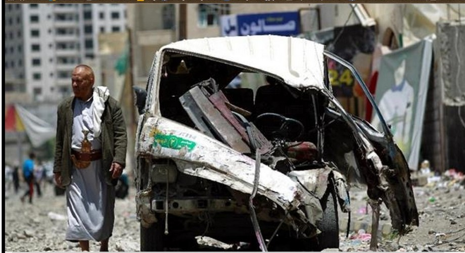 A Yemeni walks past a vehicle damaged during an airstrike by Saudi warplanes in the capital, Sana'a, 21 April 2015