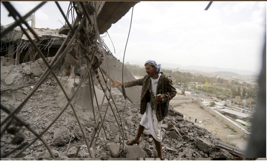 man inspects the damaged building caused by Saudi air strike in Sanaa 08 April 2015