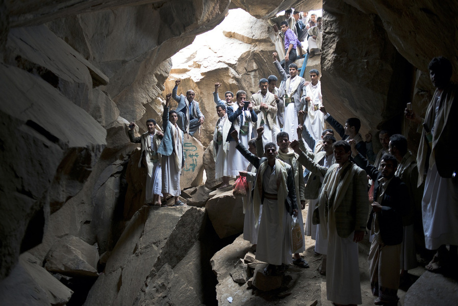Yemeni men shout the Houthi slogan - Al Sarkha (The Scream) - in the cave where former leader Hussein al Houthi was killed in Marran, Saada, Yemen, March 27, 2014. Many of al Houthi's friends were shot down from surrounding cliffs, others crushed when the cave collapsed on top of them. Marran is now a pilgrimage site for thousands of supporters each year.