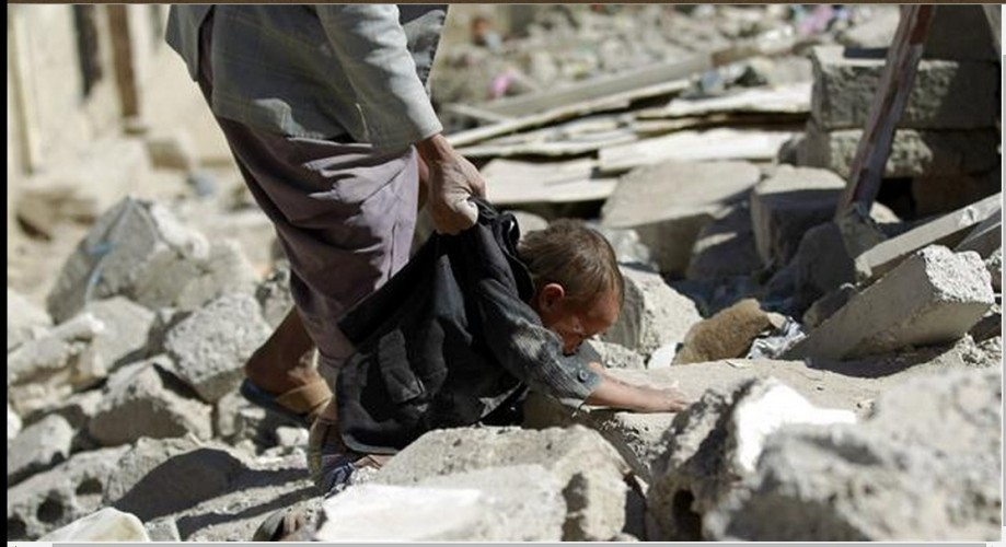 houses destroyed in an overnight Saudi airstrike on a residential area in Saan, Yemen, a child digs for his family