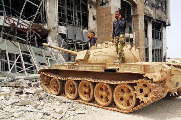 Libyan Army members on a tank in battered Benghazi