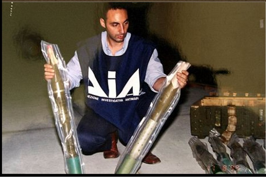 An Italian policeman of the DIA (Anti-mafia Investigation Department) holds up two Katyusha rockets from the huge cache or arms found on board the Jadran
