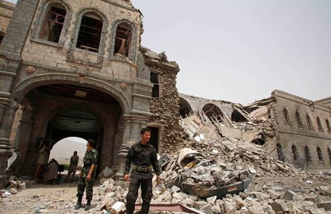 Houthi stand guard in front of Yemeni Defence Ministry building in Sana'a 10 June 2015, damaged by SAUDI airstrikes