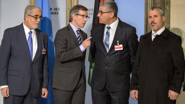 """United Nations (UN) special envoy for Libya Bernardino Leon (2nd L) speaks with one the Libya's warring factions representative Fathi Bashagha (2nd R) prior to Libyan talks on January 14, 2015 in Geneva. The United Nations began """"long and difficult"""" peace talks with Libya's warring factions in Geneva, warning they could be the last chance to prevent all-out chaos in the oil-rich country. AFP PHOTO / FABRICE COFFRINI"""