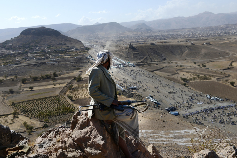 A Yemeni tribesman keeps watch from the top of a mountain during a Houthi gathering for Mawlid al Naby - birthday of the Prophet Mohammad, January 24, 2013 in Heziez, Yemen. Thousands of men and women came from around northern Yemen to hear the leader, Abdul Malik al Houthi, address the crowd on politics, religion, and the West