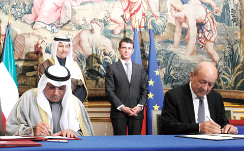 French Prime Minister Manuel Valls stands next to Kuwaiti Prime Minister